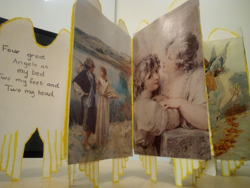 """An accordion book with images of angels with the pages cut to resemble wings. Text on the inside cover reads: """"Four great angels at my bed; two my feet, and two my head""""."""